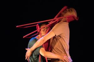 Produktion Liebe üben, ein Mann und eine Frau umarmen sich, zwischen ihnen sind Klappstühle
