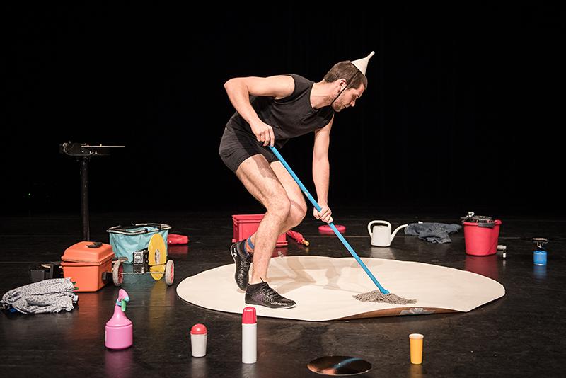 Produktion Multiverse, ein Mann mit Trichter am Kopf wischt mit einem Mop übe reinen Teppich, um ihn stehen Putzmittel