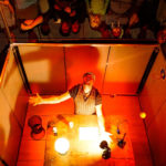 Produktion Deep, ein Mann steht in einem rot beleuchteten Quader vor einem Tisch und schaut zur Decke, seitlich sieht man Menschen, die in einem Spiegel schauen