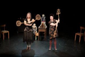 Produktion Don Quijote, zwei Frauen auf der Bühne halten Teppichklopfer in den Händen, hinter ihnen Stühle, ein Tisch und Puppen