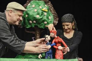 Produktion Eins Zwei Drei Vorbei, eine Frau und ein Mann führen Puppen, die sich eingehakt haben und ansehen, hinter ihnen ein Baum und eine Wiese