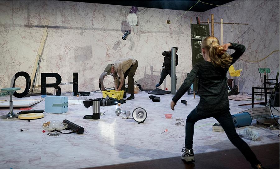Produktion Orlog Krieg, in einem Raum stehen und liegen viele Gegenstände, im hinteren Bereich zwei Männer, die mit den Gegenständen hantieren und der Schriftzug ORLOG, im vorderen Bereich ein Mädchen, das mit einer goldenen Kugel auf die Männer zielt