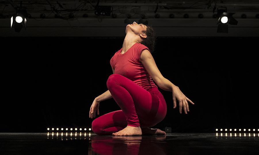 Produktion Pip. Eine Frau in roter Kleidung kniet am Boden in tänzerischer Position und hebt ihr Gesicht zur Decke
