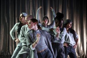 Produktion Role Model, Frauen in grauen Kostümen und roten Lippen stehen hintereinander und posieren und tanzen