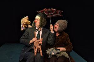 Produktion Wuff, zwei Menschen sitzen nebeneinander, sie tragen rote Cownnasen und Mützen, einer hält einen Regenschirm und sie schauen eine Hunde-Handpuppe an, zwei weitere liegen in ihrem Schoß