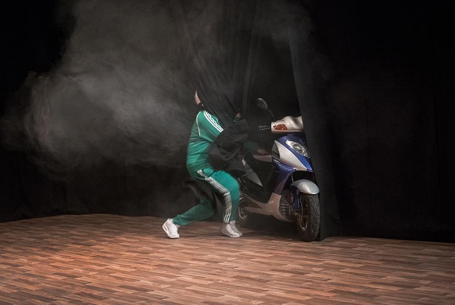 Produktion (.....), Ein Mensch in grünem Trainingsanzug ist halb vom Bühnenvorhang verdeckt, während er ein Moped schiebt, Rauch oder Abgase des Auspuffs steigen auf