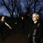 spleen*trieb Nomadenherz, drei junge Frauen hell beleuchtet vor dunklem Hintergrund mit Bäumen und Abendhimmel