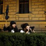 spleen*trieb Safari, zwei Menschen mit zusammengeklapptem Regenschirm und Fernglas schauen hinter einer Hecke hervor