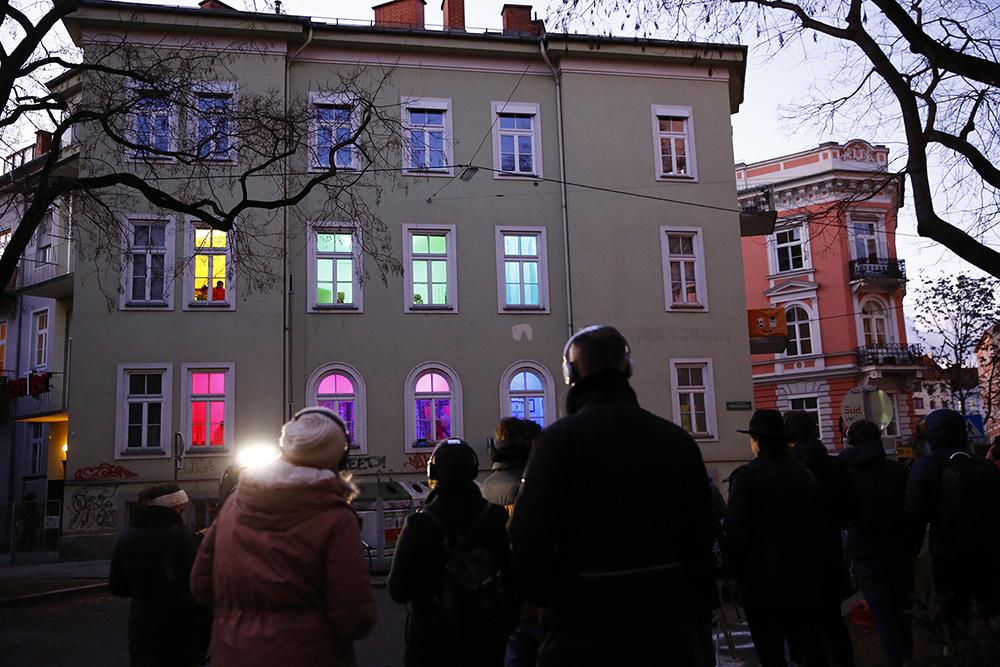 """Stück """"8 Fenster"""" Menschen stehen vor einem Haus mit bunt erleuchteten Fenstern"""