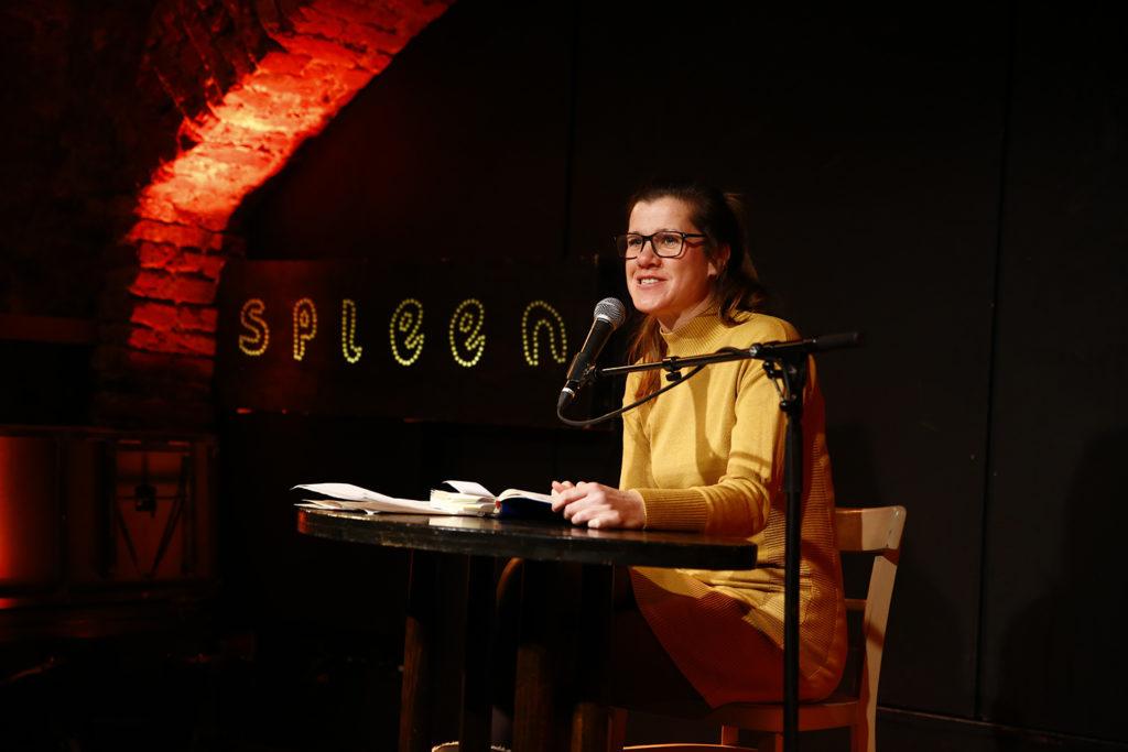"""""""Diary Slam"""", Frau sitzt auf einer Bühne und liest aus ihrem Tagebuch vor"""