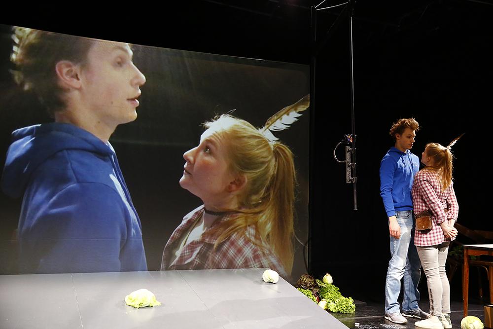 """Stück """"Die Zertrennlichen"""", Frau schaut Mann in die Augen, die Szene wird auf einen Bildschirm übertragen"""