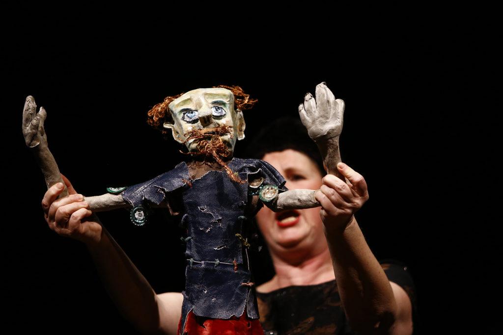 """Stück """"Don Quijote"""", Frau hält Puppe hoch, diese hat die Hände erhoben"""