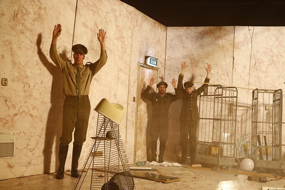 """Stück """"Oorlog Krieg"""", drei Personen stehen in einem unaufgeräumten Raum, in Militäruniform, heben die Hände"""