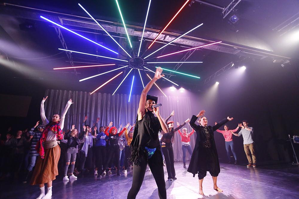 """Stück """"Role Model"""", Personen tanzen auf einer Bühne, sind bunt gekleidet"""