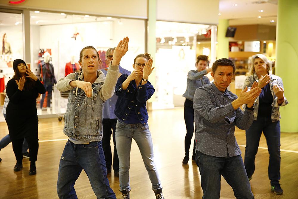 """""""Sternschnuppen und Kometen"""" aus spleen*trieb, Menschen tanzen in Einkaufszentrum, sie heban die hände gehoben und haben sich zur Kamera gedreht"""