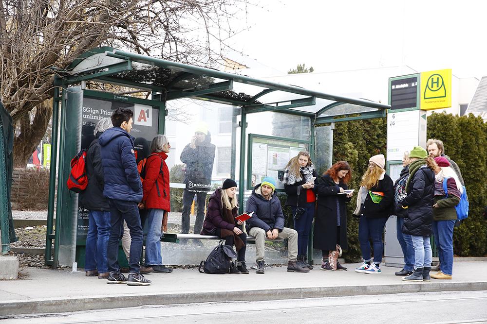 """""""Warten"""" aus spleen**trieb, Personen warten an Bushaltestelle, hören einer Person zu, die etwas vorliest"""