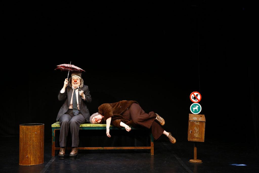 """Stück """"Wuff"""", eine Frau liegt auf einer Bank, die andere sitzt daneben und hält einen Schirm, beide tragen rote Nasen"""